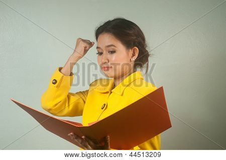 Pretty Asian Businesswoman Complacent Reading A File. poster