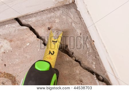 large deep crack in concrete foundation of house poster