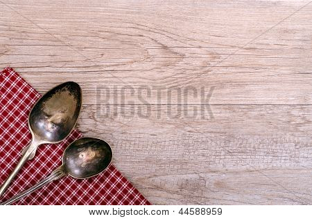 Two Old Silver Spoons On Checkered Cloth