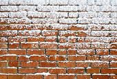 Snow sticking to an old brick wall. poster