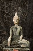Buddha on stone babkground in cave of Thailand poster