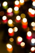 Beautiful bokeh caused by lighting candles together. poster