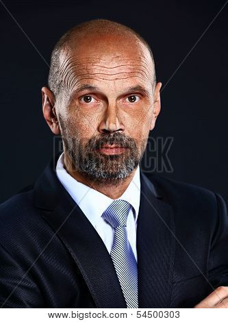 Portrait of senior confident businessman on dark background