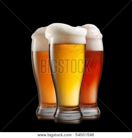 Different beer in glasses isolated on black background