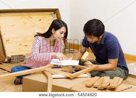 Asian couple assembling new furniture