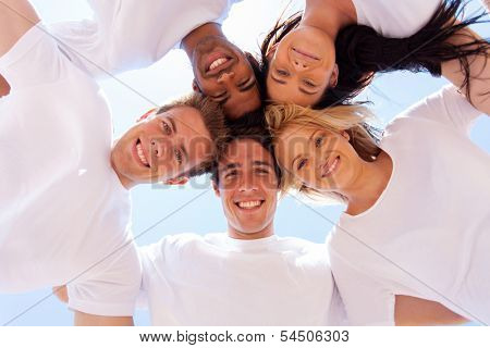 underneath view of group of friends in a circle looking down
