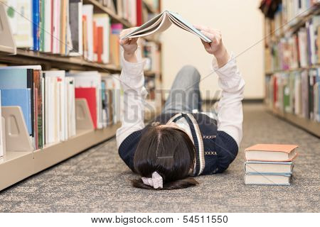 Student Laying On Floor Reading Book