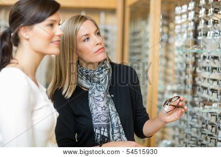Beautiful woman with salesgirl selecting eyeglasses in optician store