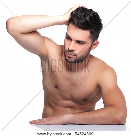 young naked man passing his hand through his hair and looking away from the camera