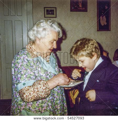 Vintage photo of great-grandmother and great-grandson blessing each other and sharing Christmas wafer during Christmas Eve Vigil, eighties