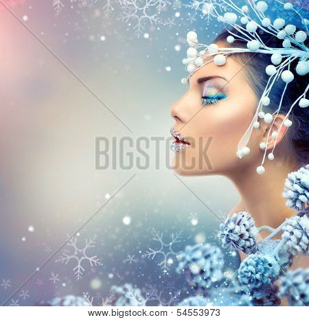 Winter Beauty Woman. Christmas Girl Makeup. Holiday Make-up. Snow Queen High Fashion Portrait over Blue Snow Background. Eyeshadows, False Eyelashes and Crystals on the Lips. Copy Space for Your Text