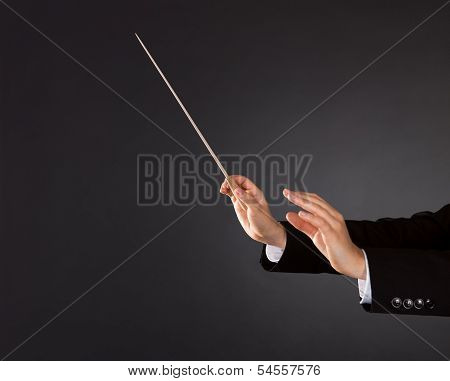 Closeup of the hands of a music conductor with a baton against a dark studio background with copyspace poster