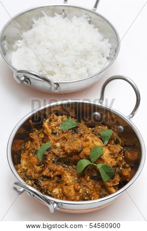 Methi murgh - chicken cooked with fresh fenugreek leaves - in a kadai, or karahi, traditional Indian wok, over white garnished with fenugreek leaves, next to a bowl of basmati rice and seen from above