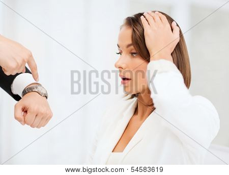 business and time management concept - boss showing watch to stressed businesswoman