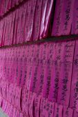 Prayer flags or prayer slips black Chinese characters on pink tissue paper at Chua Thien Hau Temple in Cho Lon Ho Chi Minh Sity Vietnam. poster