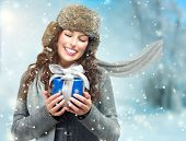 Happy Young Winter Woman With Christmas Gift. Gift Box Outdoors. Excited Girl With Holiday Present Laughing. Surprised Female. Snow poster