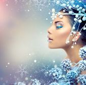 Winter Beauty Woman. Christmas Girl Makeup. Holiday Make-up. Snow Queen High Fashion Portrait over Blue Snow Background. Eyeshadows, False Eyelashes and Crystals on the Lips. Copy Space for Your Text  poster
