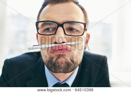 Face of funny businessman in eyeglasses holding pen between nose and lips