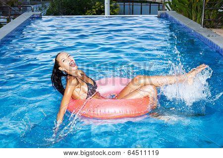 Woman Floating In Inner Tube In Pool And Having Fun
