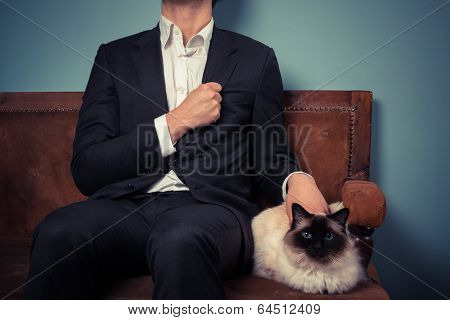 A young man is sitting with his cat on an old sofa poster