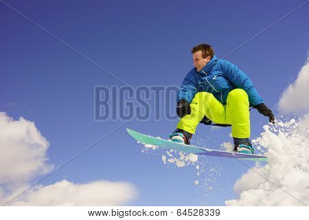 young man on the snowboard jumping over the slope in winter