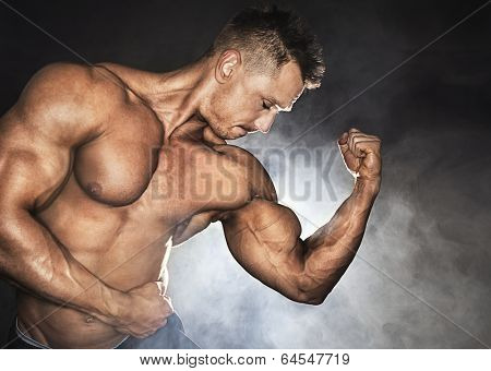 Attractive male bodybuilder showing his biceps