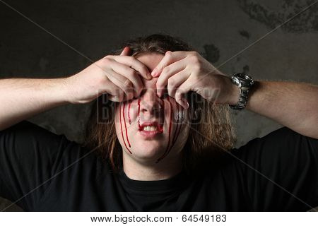 Man taking out his eyes, full of blood