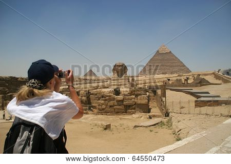 Blonde female turist takin picture of the Sphinx and the pyramids of Khafre (Chephren) and Menkaur (Mycerinus) in Giza - Cairo, Egypt