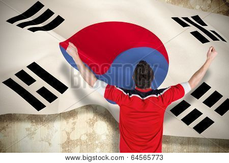 Excited football fan cheering against korea republic flag poster