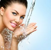 Beautiful Model Woman with splashes of water in her hands. Beautiful Smiling girl under splash of water with fresh skin over blue background. Skin care, Cleansing and moisturizing concept. Beauty face poster