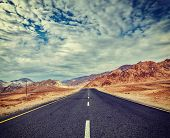 Vintage retro effect filtered hipster style travel image of Travel forward concept background - road in Himalayas with mountains and dramatic clouds. Ladakh, Jammu and Kashmir, India poster