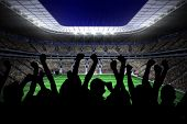 Silhouettes of football supporters against large football stadium with lights poster