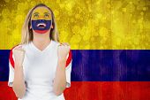 Excited colombia fan in face paint cheering against colombia flag in grunge effect poster