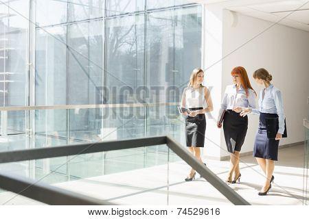 Full-length of businesswomen walking at office hallway