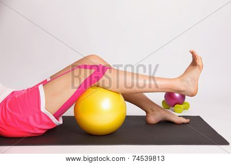 Woman With Injured Knee Doing Physiotherapy Exercise with Kinesiology tape poster