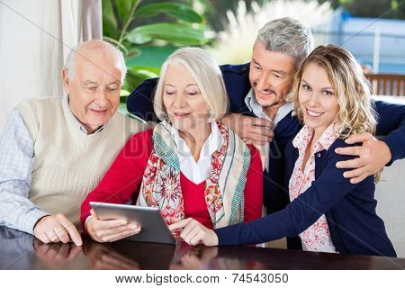 Portrait of smiling young woman using digital tablet with family at nursing home