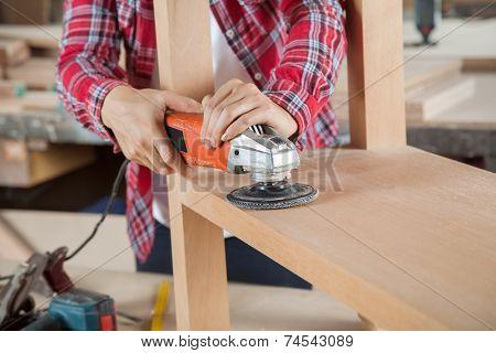 Midsection of female carpenter using sander on wood in workshop