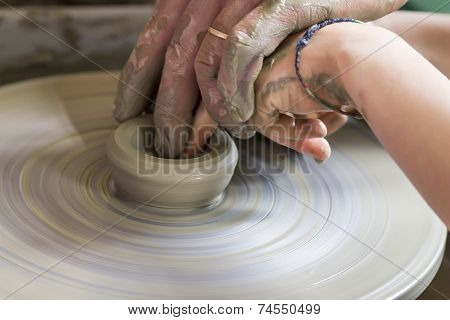 Potter shaping a ceramic plate on a pottery wheel