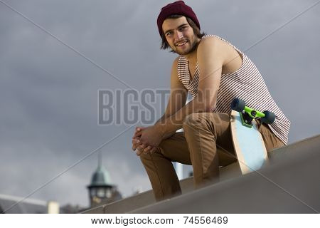 Urban lifestyle portrait of a streetwise skateboarder, sitting on concrete steps