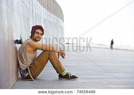 Streetwise youth, sitting carefree against the granite wall of a boardwalk looking difiantly into the camera, with his skateboard next to him