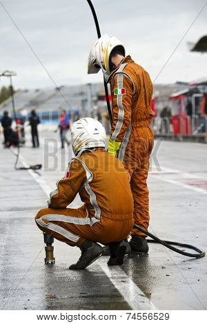 Pit Crew anticipating the arrival of their race car during a tyre change pitstop because of wet race conditions