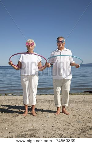 Outdoor photo of retired couple with hula-hoops and silly glasses