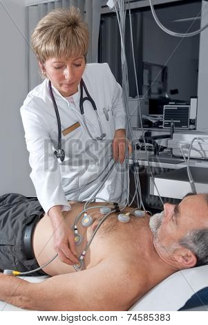 doctor makes the elderly patient ready for  EKG test
