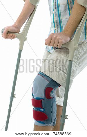 Bandage on knee of man's on crutches
