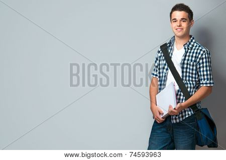 Smiling teenager with a schoolbag standing on wall background