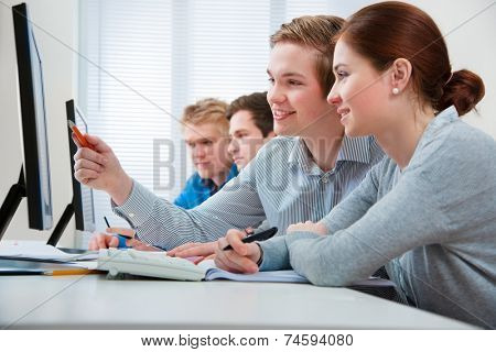 Group of students attending training course in a computer classroom
