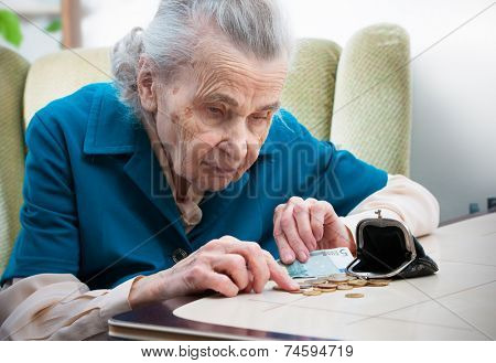 elderly caucasian woman counting money  on table