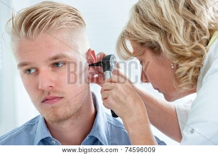 ENT physician looking into patient's ear with an instrument