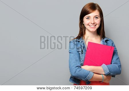Young woman holding job application on grey background