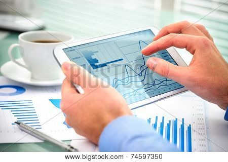 Close-up of businessman using tablet computer to work with financial data